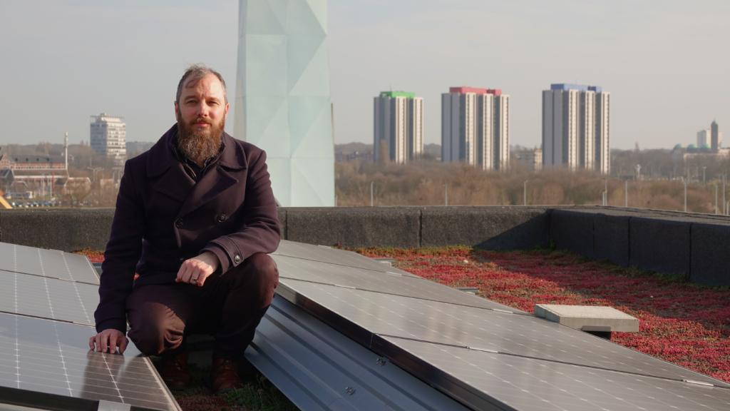 Jan Wouters op een dak van één van onze gebouwen op Nieuw Zuid. Op het dak staan zonnepanelen. Op de achtergrond staat de verwarmingstoren die de wijk van warm water voorziet.