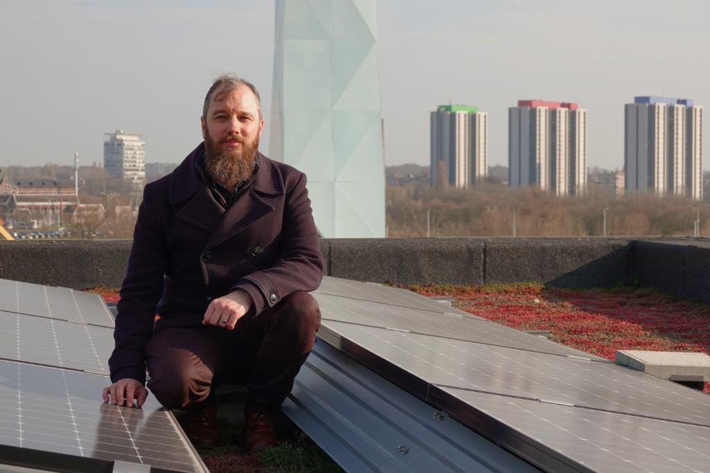 Jan Wouters op het dak van een gebouw op Nieuw Zuid naast zonnepanelen en de verwarmingstoren op de achtergrond